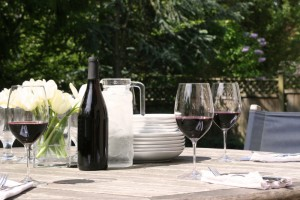 An outdoor table set with plates and red wine