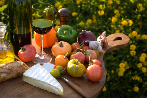 Cutting board with summer ingredients, cheese, and wine