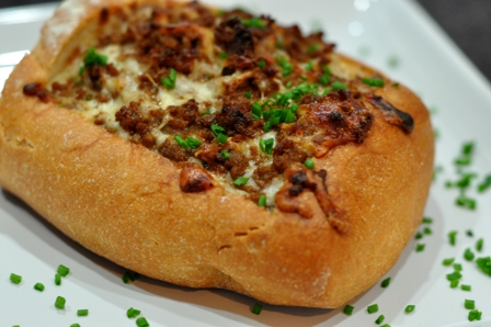 Bread stuffed with cheese and chorizo, garnized with chives