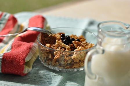 Granola with milk, spoon, and a brightly colored napkin