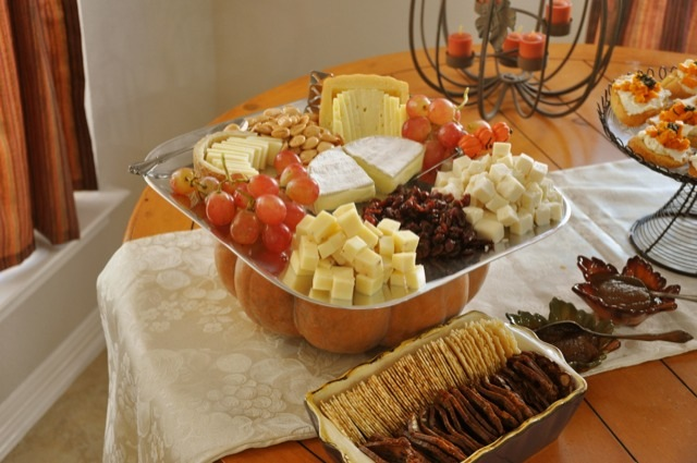 A pumpkin becomes as pedestal for a cheese plate at a fall party